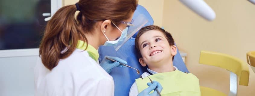 Pediatric Dentist looking at patient